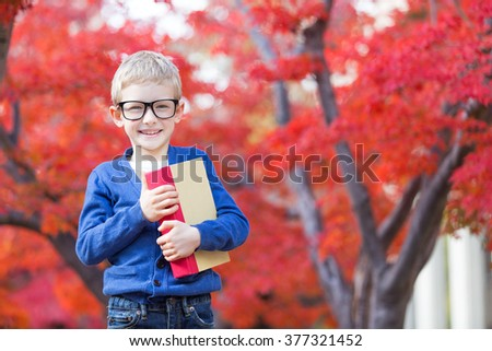 cheerful schoolboy in glasses holding book and ready for school, beautiful japanese red maple tree in the background - stock photo
