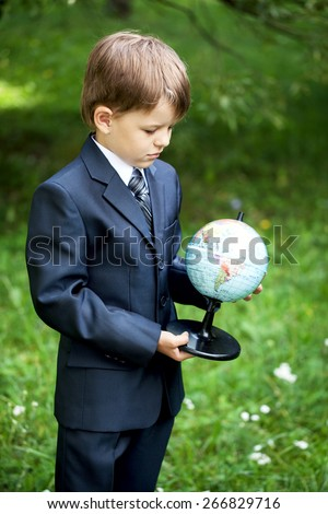 Cheerful schoolboy pointing at the globe in his hands outdoors - stock photo