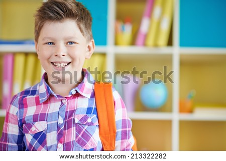 Cheerful schoolboy with backpack looking at camera - stock photo