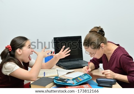 Cheerful schoolgirl teen teases her teacher - stock photo