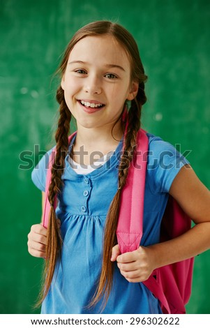 Cheerful schoolgirl with backpack looking at camera - stock photo