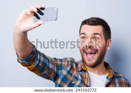 Cheerful selfie. Cheerful young man in shirt holding mobile phone and making photo of himself while standing against grey background - stock photo