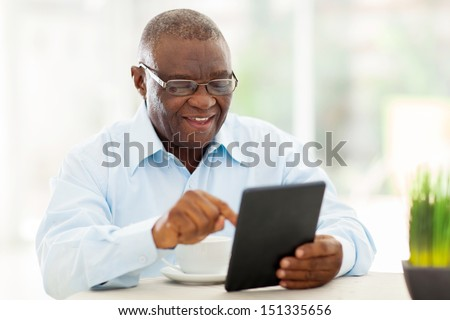 cheerful senior african american man using tablet computer at home - stock photo