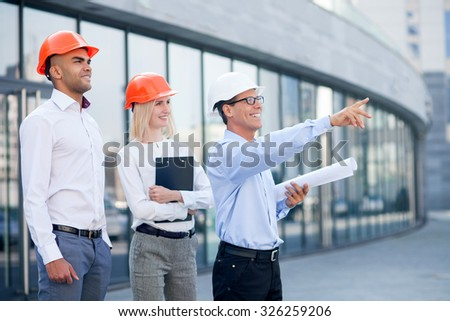 Cheerful senior architect is explaining to builders his plan of construction. He is holding blueprint and pointing finger at building. The man and woman are standing and smiling - stock photo