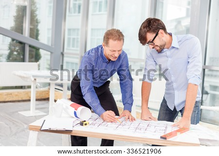 Cheerful senior architect is explaining to his young colleague the plan of building. The men are looking at the blueprint on the table with aspiration. They are standing and smiling