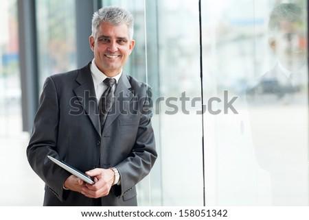 cheerful senior businessman leaning on office window - stock photo