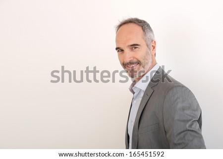 Cheerful senior businessman standing on white background - stock photo