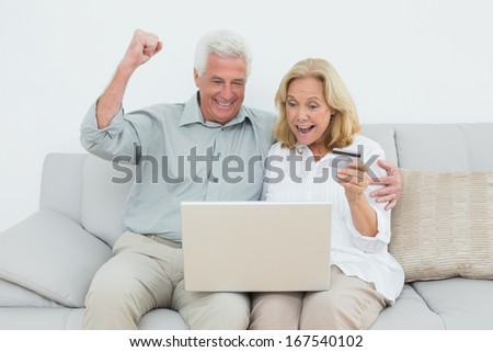 Cheerful senior couple doing online shopping through laptop and credit card on sofa in a house