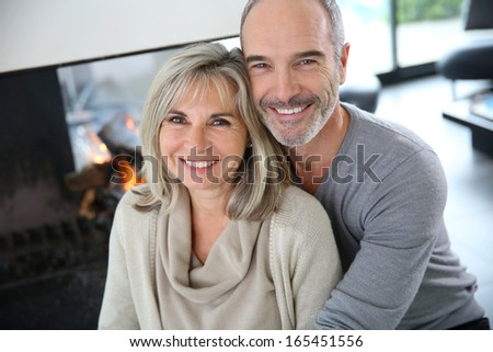 Cheerful senior couple enjoying fireplace in winter - stock photo