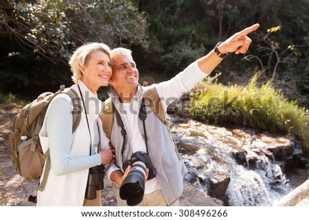 cheerful senior couple hikers pointing in mountain valley