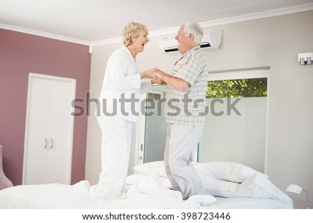 Cheerful senior couple jumping on bed in room - stock photo