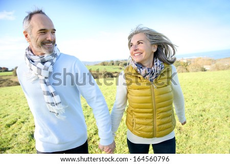 Cheerful senior couple running in countryside - stock photo