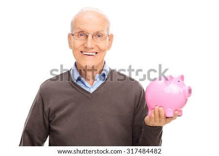 Cheerful senior gentleman holding a pink piggybank and looking at the camera isolated on white background - stock photo