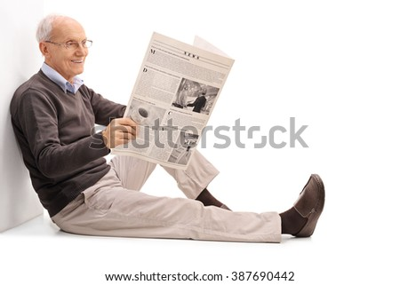 Cheerful senior gentleman reading a newspaper seated on the floor isolated on white background - stock photo