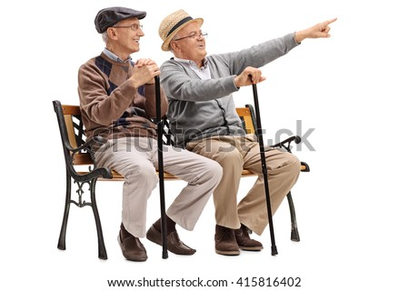 Cheerful senior gentleman showing something to an old friend seated on a bench isolated on white background