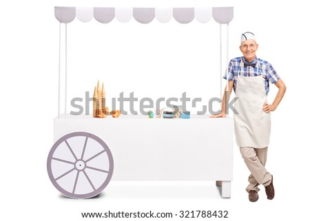 Cheerful senior ice cream vendor posing next to a stall with waffle cones and other candy on it isolated on white background - stock photo