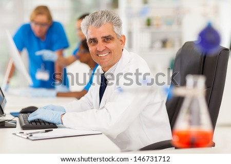 cheerful senior lab technician working on computer - stock photo
