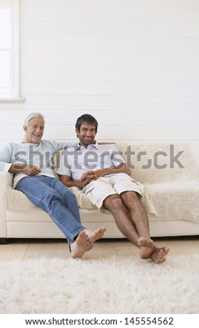 Cheerful senior man with son relaxing on sofa at home