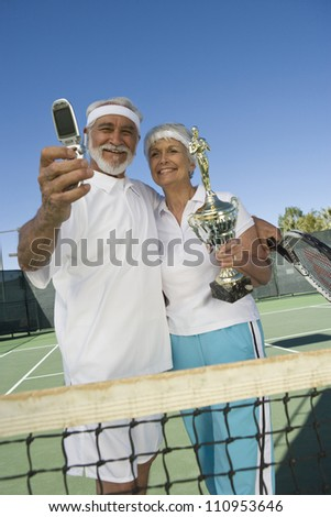 Cheerful senior tennis player holding trophy after winning - stock photo