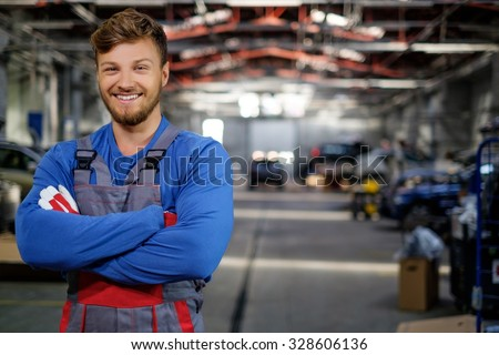 Cheerful serviceman in a car workshop - stock photo