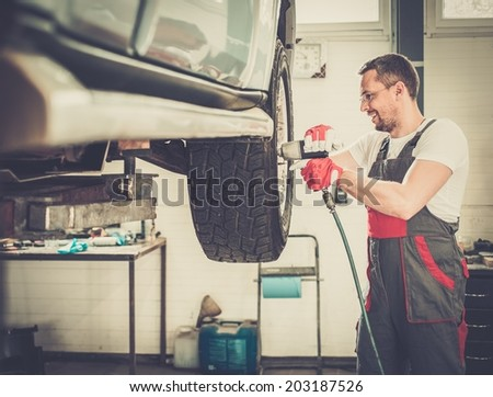 Cheerful serviceman unscrewing wheel in car workshop  - stock photo