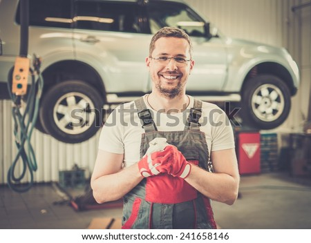 Cheerful serviceman wearing overall in car workshop  - stock photo