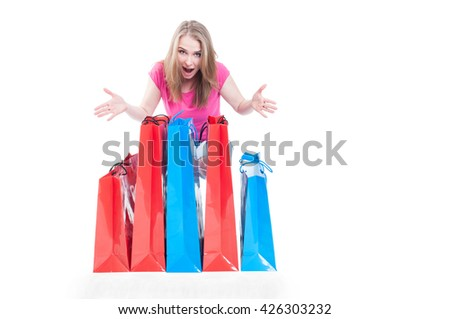 Cheerful shopaholic woman with many present or shopping bags smilling happily with copyspace isolated in white - stock photo