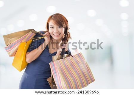 Cheerful shopping woman of Asian holding bags.