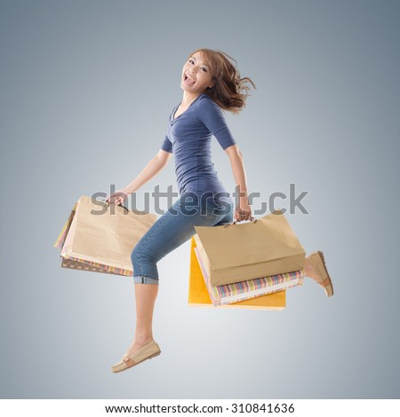 Cheerful shopping woman of Asian holding bags, isolated. - stock photo