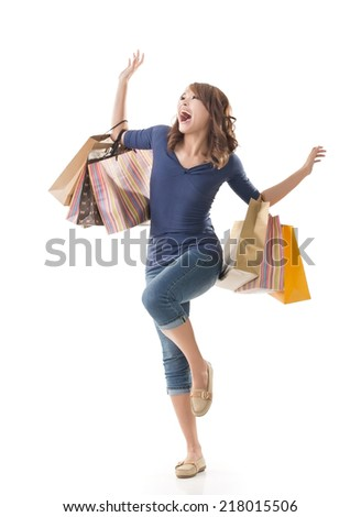 Cheerful shopping woman of Asian holding bags on white studio background. - stock photo