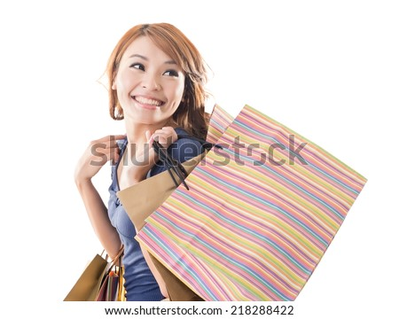 Cheerful shopping woman of Asian holding bags on white studio background.