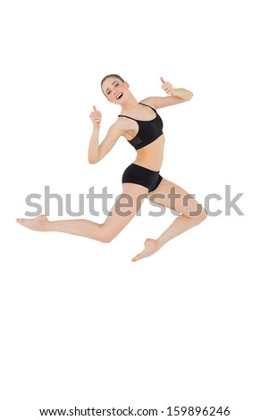 Cheerful slim model jumping in the air on white background - stock photo