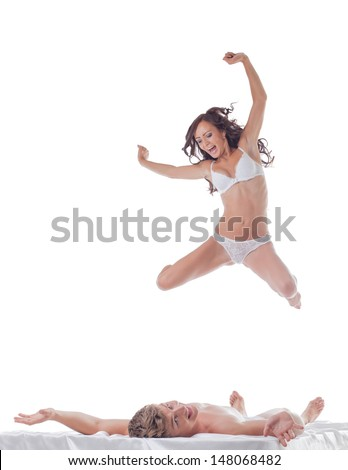 Cheerful slim woman jumping into bed with sexy guy - stock photo
