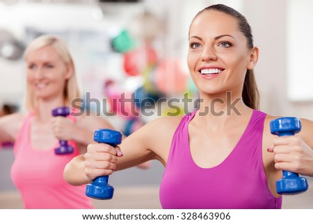 Cheerful slim women are exercising with weights in fitness center. They are sitting and smiling. The ladies are looking forward with happiness - stock photo