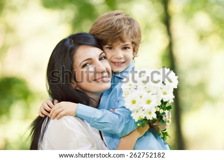 Cheerful smiling boy (child, kid) and woman with bouquet of  flowers playing on spring park. Mother`s day concept
