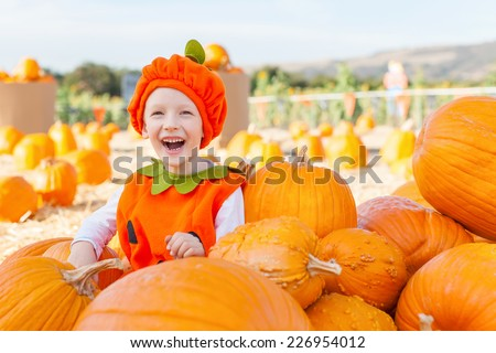 cheerful smiling boy in the pumpkin costume at pumpkin patch, autumn fun - stock photo