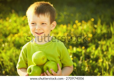 Cheerful smiling boy with green apples. child with fruit on a green background - stock photo