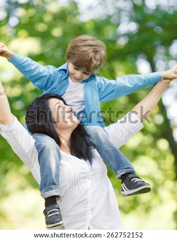 Cheerful smiling boy with mother playing on spring park. Mother`s day concept