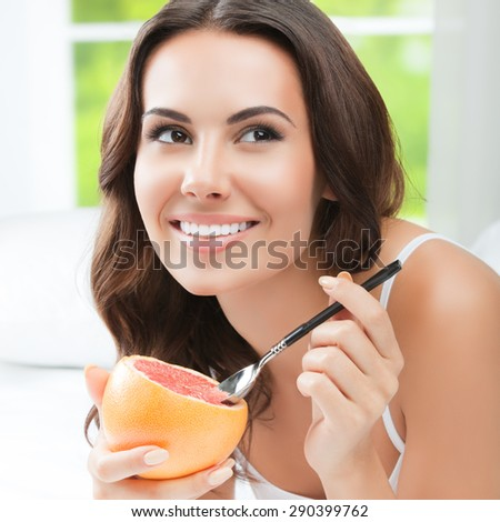 Cheerful smiling brunette woman eating grapefruit at home. Healthy eating, beauty and dieting concept. - stock photo