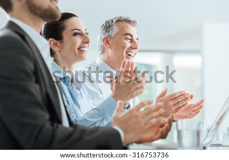 Cheerful smiling business people clapping hands during a seminar, success and achievement concept - stock photo