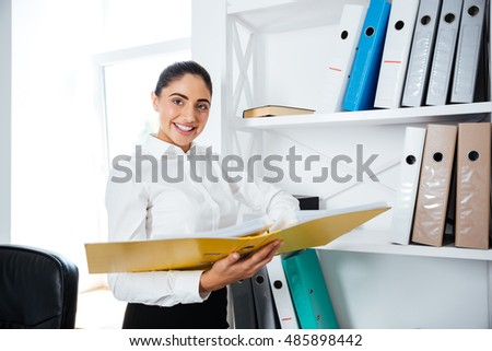 Cheerful smiling businesswoman standing and holding yellow folder at the office