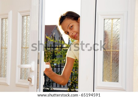 cheerful smiling caucasian teenage girl behind opened white front door looking inside - stock photo
