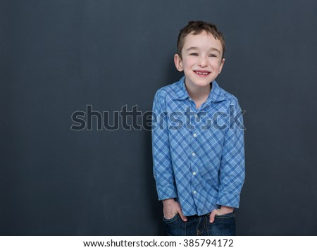 Cheerful smiling child at the blackboard