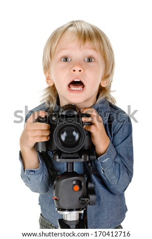 Cheerful  smiling  child (boy) holding a camera on tripod - stock photo