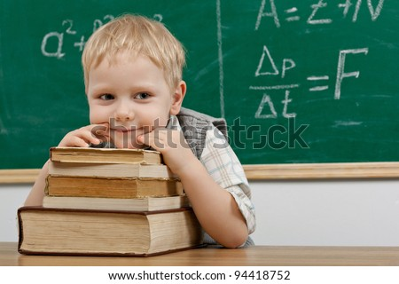 Cheerful smiling   child resting on a stack of books in a classroom. Looking at camera. School concept - stock photo
