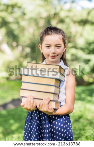 Cheerful smiling children girl hold chalkboard at the park . School learning concept at the park . School learning concept - stock photo