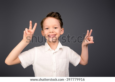 Cheerful smiling comic boy gesturing with two fingers - stock photo