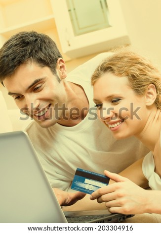 Cheerful smiling couple paying by plastic card with laptop, indoors
