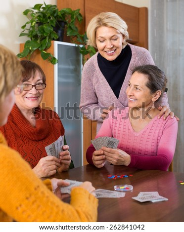 Cheerful smiling female pensioners playing cards at home - stock photo