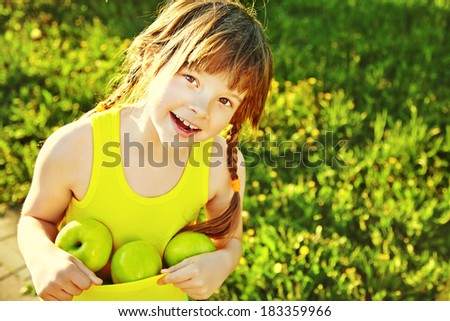 Cheerful smiling girl with green apples. child with fruit on a green background - stock photo